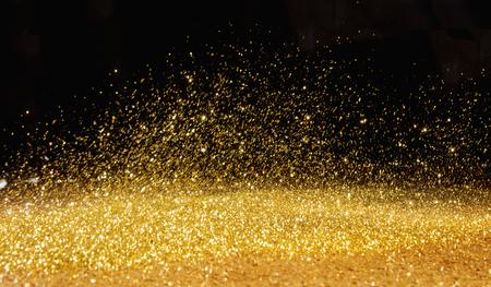 Golden, shining powder scattered over the dark background
