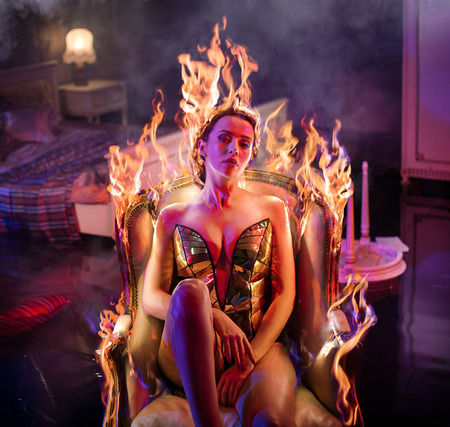 Sensual woman relaxing in the burning, antique armchair Фото со стока