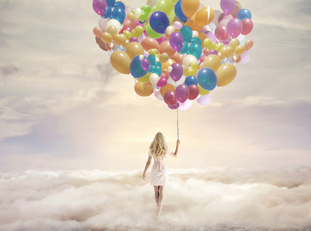 Conceptual picture of a woman holding hundreds of colorful balloons