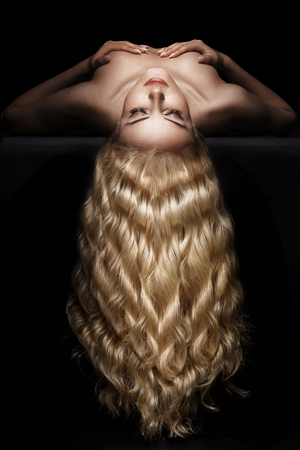 Delicate blond woman with long, wavy hairstyle