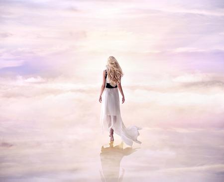 Immagine concettuale di una donna bionda che cammina sulle nuvole delicate e soffici