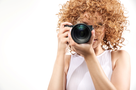 Attractive frizzy-haired woman taking a photograph Stok Fotoğraf