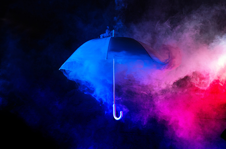 Abstract concept - a blue umbrella among colorful dust clouds