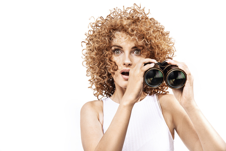 Amazed redhead woman looking throug the binoculars