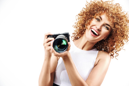 Cheerful frizzy-haired woman holding a digital camera