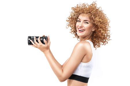 Commercial style portrait of a redhead, frizzy-haired woman holding a camera Stok Fotoğraf