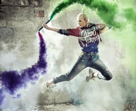 Flexible blond girl dancer holding a colorful flare