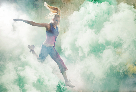 Portrait of a jumping girl-dancer holding colorful flares