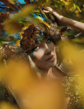 Art portrait of a blond nymph posing in the autumnal park