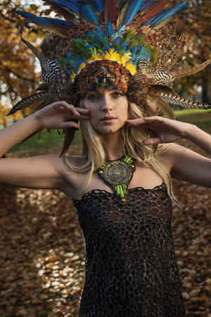 Pretty blond woman wearing coronet made of peacocks feathers