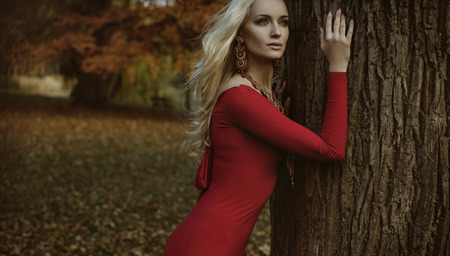 Pretty blond woman posing in an autumnal forest