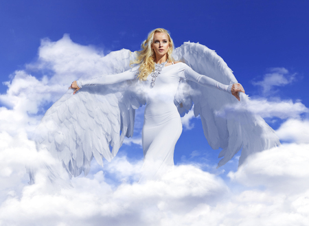 Conceptual portrait of a young, blond angel flying up to the sky