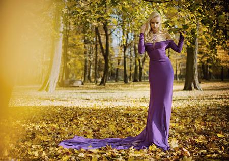 Elegant, sensual woman walking in the autumnal park
