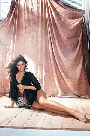 Portret van een sensuele latina-vrouw die op een houten vloer ligt