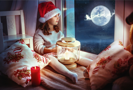 Cute, little girl looking at the moon the winter sky Imagens - 116331522