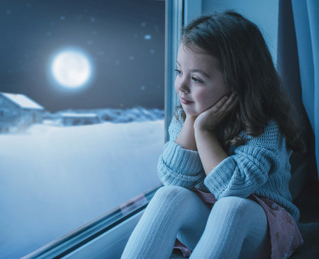 Cute, little girl looking at the moon the winter sky Stock Photo