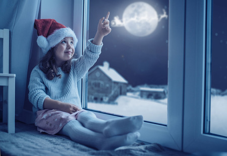 Cute, little girl looking at the moon the winter sky Imagens