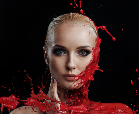 Red paint splashing against a womans young face Stock Photo