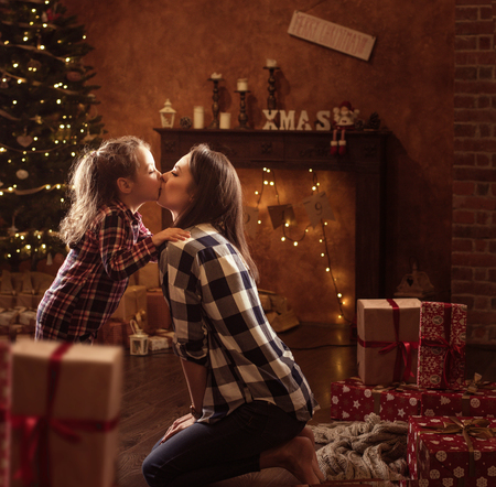 Conceptual portrait of a mother kissing a little daughter, christmas items in background