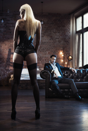 Handsome businessman looking at the sensual woman wearing lingerie