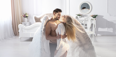 Conceptual portrait of an archangel embracing a beautiful, blond woman