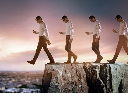 conceptual portrait of a young, successful businessman falling down from the cliff