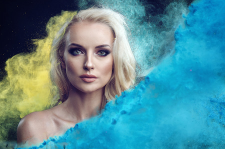 Closeup portrait of an charming blonde among blue and yellow powder cloud