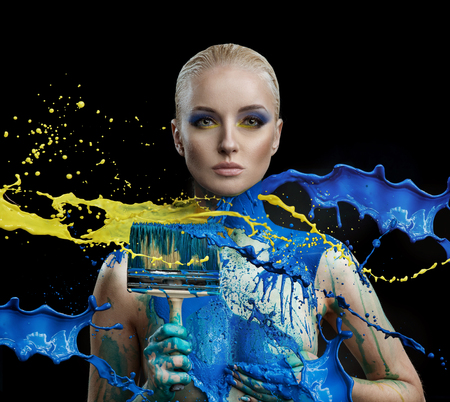 Blond woman covered by blue and yellow paint holding a brush