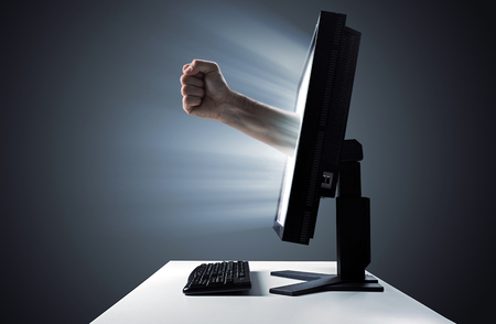 Male fist emerging out of the display monitor- violent in the Internet symbol