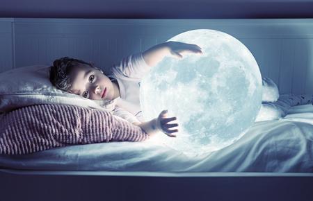 Art portrait of a cute little girl holding a shining moon