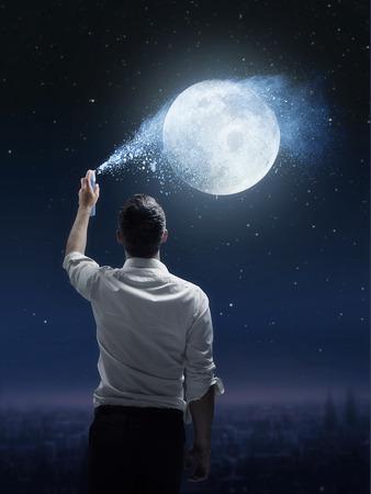 Conceptual portrait of a joyful man sprinkling a moon
