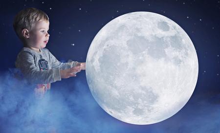 Art portrait of a cute, little boy holding a moon