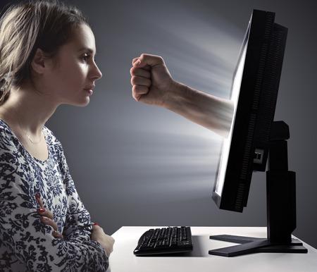Pretty woman looking at the monitor - Internet violence symbol Banco de Imagens