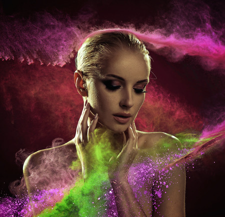 Pretty blond woman covered with colorful powder