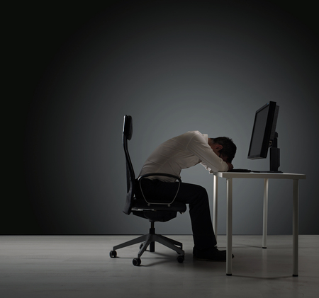 Exhausted businessman having a nap on the desk