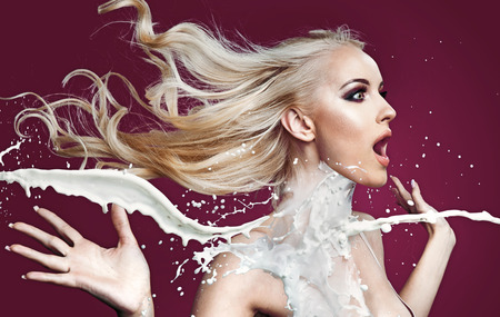 Amazed blond woman being poured with white paint