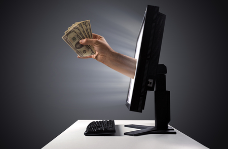 Bunch of money jumping out of the display - Internet trade sign Banco de Imagens