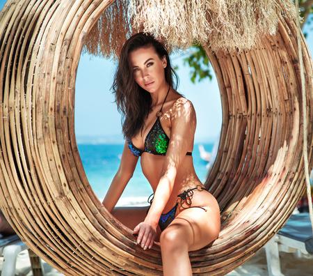 Sensual brunette woman relaxing on a bamboo circle - swing Banco de Imagens