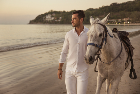 Handsome, young guy walking with a stallion alongside the coast Banco de Imagens