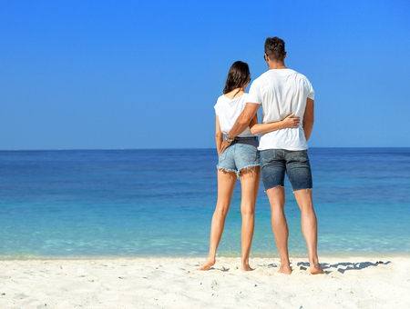 Young, attractive couple relaxing on a hot, tropical beach