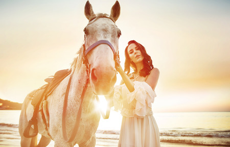 Beautiful, young woman with a calm stallion