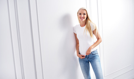 Young, blond woman leaning on a decorative wall