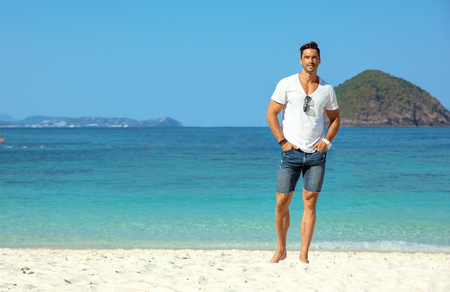 Handsome, muscular guy relaxing on a tropical beach