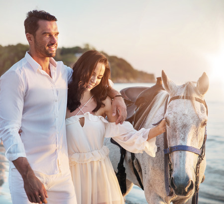 Young couple walking a majestic, white horse - seaside landscape