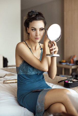 Beautiful lady doing make-up in the bedroom Banco de Imagens
