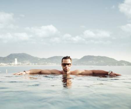 Portrait of a serious man relaxing in a tropical pool Banco de Imagens