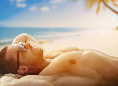 Handsome, muscular guy, relaxing on a tropical beach Banco de Imagens