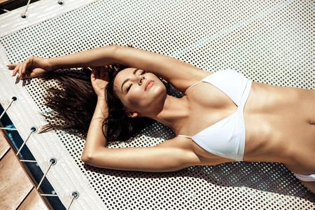 Sensual young woman relaxing by the tropical pool Banco de Imagens