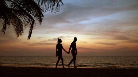 Attractive, young couple relaxing and walking on a tropical beach Imagens