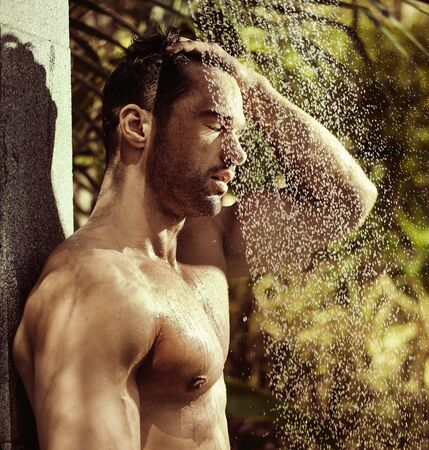 Handsome, young man taking a tropical shower